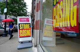 FILE - In this Sept. 2, 2020, file photo, a passerby walks past a business storefront with store closing signs in Boston. The U…