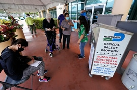 Voters prepare to turn in their mail-in ballots, Oct. 6, 2020, at the Miami-Dade County Elections Department in Doral, Florida.