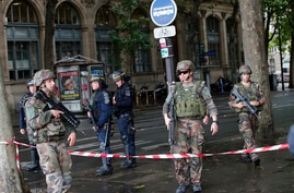 FILE - In this June 6, 2017 file photo, police officers and soldiers seal off the access to Notre Dame cathedral after a man…