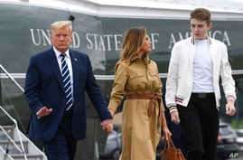 FILE - In this Aug. 16, 2020 file photo, President Donald Trump, first lady Melania Trump and their son, Barron Trump, walk off of Marine One and head toward Air Force One at Morristown Municipal Airport in Morristown, N.J.