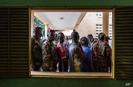 Civilians and soldiers line up to vote at a school in Conakry, Guinea, Sunday Oct. 18, 2020. Guineans head to the polls to…