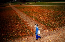 A woman, wearing a face mask to prevent the spread of the coronavirus COVID-19, walks along Cinquantenaire park in an autumn…