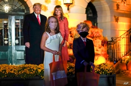President Donald Trump and first lady Melania Trump poses for a photo with children dressed as them as they greet trick-or…