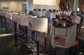 Voters cast their ballots at privacy booths during early voting at the Brooklyn Museum, Tuesday Oct. 27, 2020, in New York. (AP…