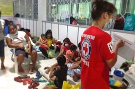 In this handout photo provided by the Philippine Red Cross, families stay at a temporary evacuation center at Catanduanes…