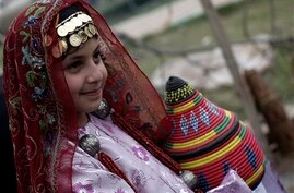 A Yemeni girl wearing traditional costume, poses for a picture during the opening ceremony of Sanaa Summer Festival in Sanaa,…