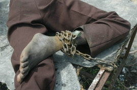 A patient from the Holy Ghost Mental Home sits, while chained to a table in Monrovia, Liberia,  Friday, Aug. 29, 2003 where a…