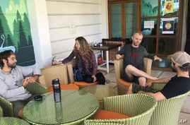 Australian tourist Stewart Dufty, 44, second right, talks with other stranded foreign tourists at a hostel in New Delhi, India, April 2, 2020.