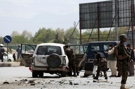 FILE - Afghan security forces inspect the site of a bomb explosion near a damaged vehicle in Kabul, Afghanistan,, April 27, 2020.