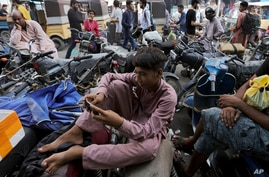 A youngster uses the social media app Tik Tok on his phone, at a market in Karachi, Pakistan, Tuesday, July 21, 2020. Pakistan…
