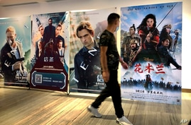 "A man wearing a face mask walks past a poster for the Disney movie ""Mulan"" at a movie theater in Beijing, on Sept. 11, 2020."