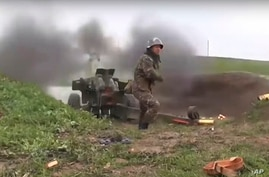 This image taken from a video released by Armenian Defense Ministry on Friday, Oct. 2, 2020 an Armenian serviceman fires a…