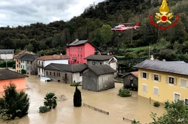 A firefighters' helicopter flies over flooding in the town of Ornavasso, in the northern Italian region of Piedmont, Oct. 4, 2020.