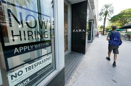 """A pedestrian walks past a Zara store with a large """"Now Hiring,"""" sign in the window, Oct. 12, 2020, along the famed Lincoln Road area in Miami Beach, Florida."""