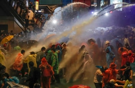 Pro democracy demonstrators face water canons as police try to clear the protest venue in Bangkok, Thailand, Friday, Oct. 16,…