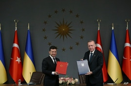 Turkish President Recep Tayyip Erdogan, right, and Ukrainian President Volodymyr Zelenskiy pose for photographs after they…