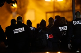 French police officers gather outside a high school after a history teacher who opened a discussion with students on…