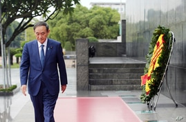 Japanese Prime Minister Yoshihide Suga leaves after laying a wreath at the mausoleum of Vietnam's late President Ho Chi Minh in Hanoi, Vietnam, Oct. 19, 2020.