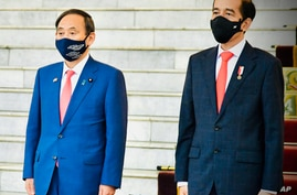 In this photo released by Indonesian Presidential Palace, Japanese Prime Minister Yoshihide Suga, left, and Indonesian…