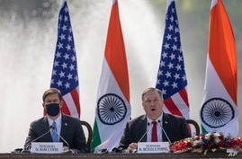 U.S. Secretary of State Mike Pompeo, right, speaks with Secretary of Defence Mark Esper seated beside him during a joint press conference with their Indian counterparts at Hyderabad House in New Delhi, India, Oct. 27, 2020.