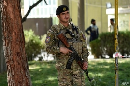 An Afghan policeman stands guard in the courtyard of the police headquarters in Kabul, Oct. 12, 2020.