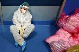 A medical worker in personal protective equipment (PPE) rests at the COVID 3 level Intensive Care Unit (ICU) at the Casal Palocco hospital, near Rome, Italy.