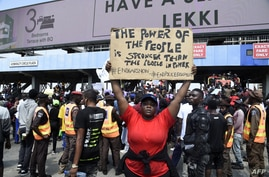 A demonstrator holds a placard to protest against abuses by the Special Anti-Robbery Squad (SARS) at the Lekki toll Plaza in Lagos, Nigeria, Oct. 12, 2020.