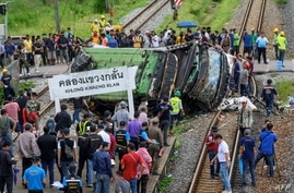 Officials and onlookers gather near the wreckage of an overturned bus involved in a deadly collision with a train next to Khlong Kwaeng Klan railway station in Chachoengsao province, east of the Thai capital Bangkok, Oct. 11, 2020.