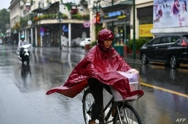 FILE - A woman in a poncho rides a bicycle during heavy rainfall in Hanoi, Oct. 14, 2020, as tropical storm Nangka made landfall in north-central Vietnam.