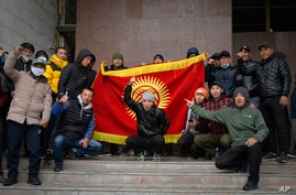 Protesters hold up a national flag at Kyrgyz government headquarters, in Bishkek, Kyrgyzstan, Oct. 6, 2020.