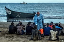 Migrants from Morocco have their temperature checked because of the coronavirus, upon arrival at the coast of the Canary Island, Spain, after crossing the Atlantic Ocean sailing on a wooden boat, Oct.20, 2020.