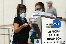 An election worker places a vote-by-mail ballot into an official ballot drop box outside of a voting site in Miami Florida. (Lynne Sladky/AP)
