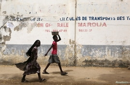 FILE - Girls walk on a road in Maroua, Cameroon, March 17, 2016. Amid misconceptions and skepticism surrounding HPV vaccinations in the country, efforts are underway to educate parents about the importance of having girls vaccinated.