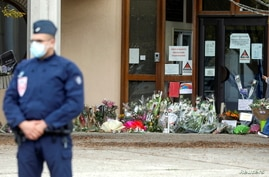 Flowers are stacked outside the school where slain history teacher Samuel Paty was working, in Conflans-Sainte-Honorine, northwest of Paris, France, Oct. 17, 2020.
