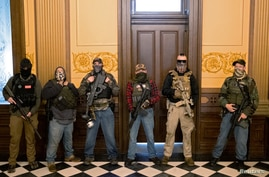 FILE - Armed members of a militia group stand in front of the Governor's Office after protesters occupied the state capitol building in a protest against the policies of Governor Gretchen Whitmer, at the state capitol in Lansing, Michigan, April 30, 2020.