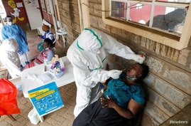 Health workers collect swab samples during free mass testing for the COVID-19 in Kibera slums of Nairobi, Kenya, Oct. 17, 2020.