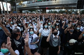 Pro-democracy protesters show the three-finger salute during an anti-government protest, in Bangkok, Thailand, Oct. 19, 2020.