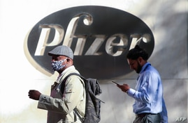 People walk by the Pfizer world headquarters in New York on November 9, 2020. - Pfizer stock surged higher on November 9, 2020…