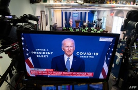 President-elect Joe Biden speaks about coronavirus as he appears on a television in the Brady Press Briefing Room of the White…