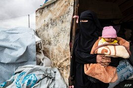 A Syrian woman carrying a baby looks out of a tent as she packs her belongings before leaving the Kurdish-run al-Hol camp…