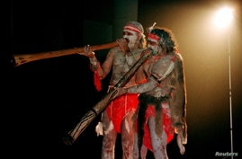 Two Aboriginal performers painted in traditional colours play the 'Didjiridoo' aboriginal instrument at the launch of the …
