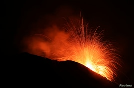FILE - Lava spurts from the Stromboli volcano a day after an eruption unleashed a plume of smoke on the Italian island of Stromboli, Italy, Aug. 30, 2019.