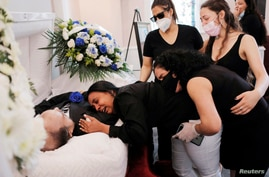 Maria Ortiz embraces the body of her partner Jose Holguin, 50, who died of complications related to COVID-19, New York City, May 16, 2020.