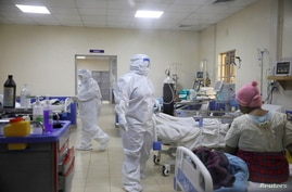 Medical staff dressed in protective suits treat coronavirus disease patients at the COVID-19 ICU of Machakos Level 5 Hospital,…