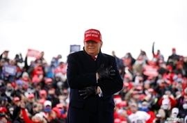 U.S. President Donald Trump reacts to cold weather and wind during a campaign rally at Michigan Sports Stars Park in Washington…