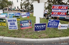 FILE PHOTO: Campaign signs are posted near the Supervisor of Elections Office polling station while people line up for early…