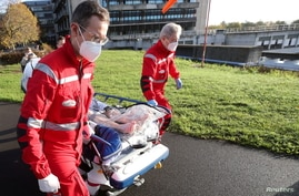 A patient infected with the coronavirus disease (COVID-19) is transported in a plastic cover to a medical helicopter.