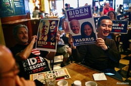 People hold posters and campaign signs for U.S. Democratic presidential nominee Joe Biden and running mate, Kamala Harris.