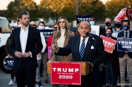 Former New York City Mayor Rudy Giuliani, personal attorney to U.S. President Donald Trump, speaks near Eric Trump and his wife.