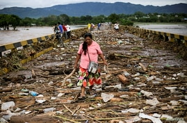 A woman walks among debris on a bridge over the Chamelecon river after the passage of Storm Eta, in Pimienta, Honduras Nov. 6, 2020.
